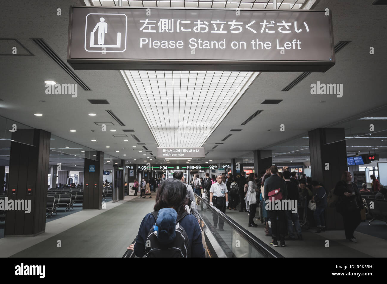Passengers walking in the departure terminal of Narita International Airport with belonging - Stock Image