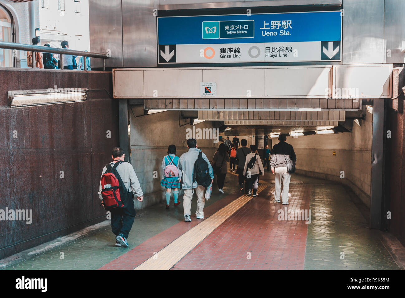 People entering Ueno subway station through entrance carrying their backpack Stock Photo