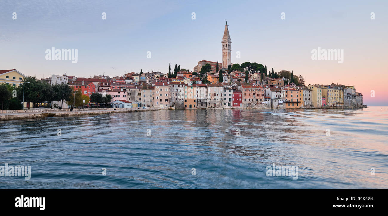 View of the city of Rovinj in Croatia.  Sunrise light on the old town reflecting in harbor. - Stock Image