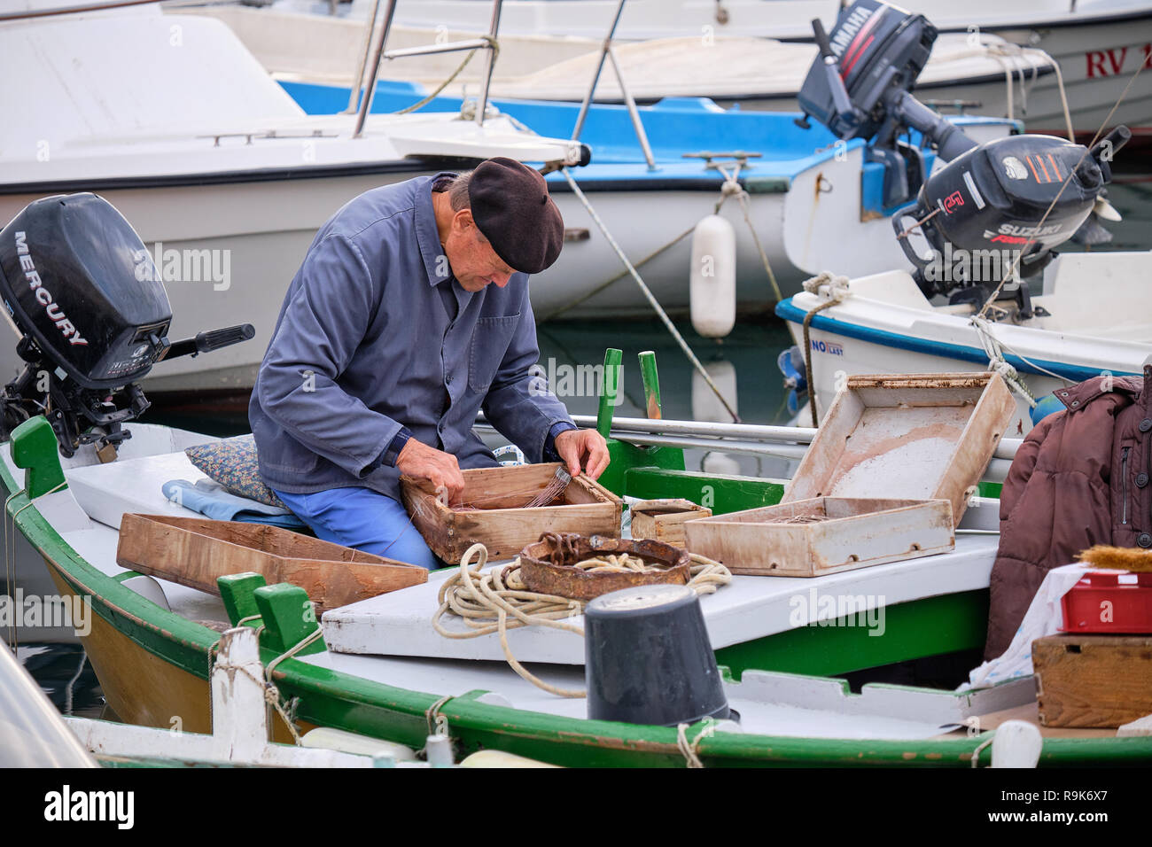 Fisherman wearing frock and beret in harbour of Roving, preparing and organising his box of tackles before going to sea - Stock Image