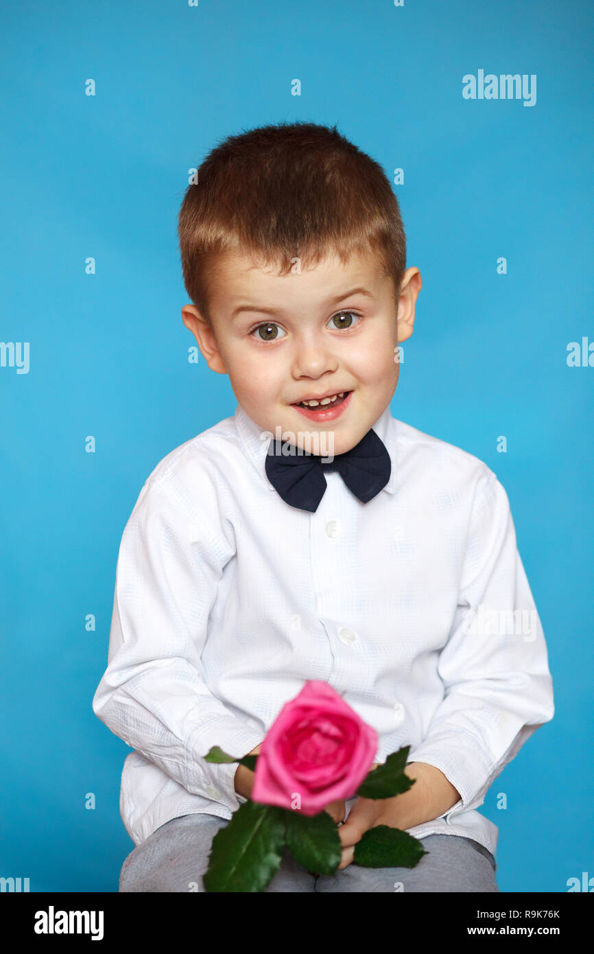 f0d9de80264c A cute little boy holds a flower in his hand. Concept of holidays, greetings