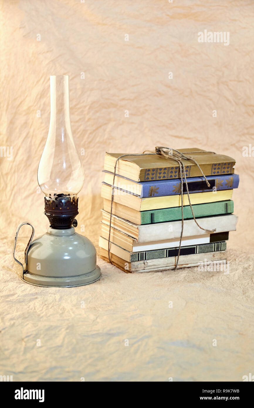 Kerosene lamp and stack of old books tied up with string. - Stock Image