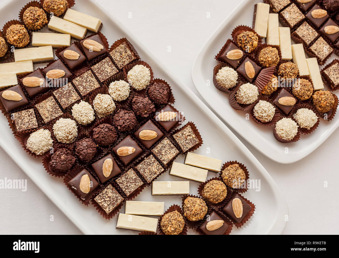 Small chocolate and vanilla layered cakes in rows on candy buffet. Sweet paradise. Top view. - Stock Image