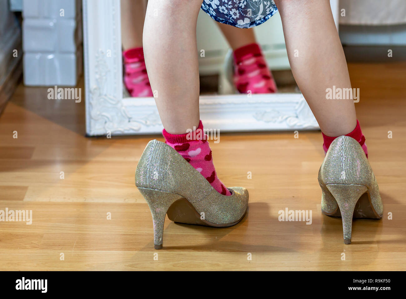 Little girl wearing big high-heeled mother's shoes. - Stock Image