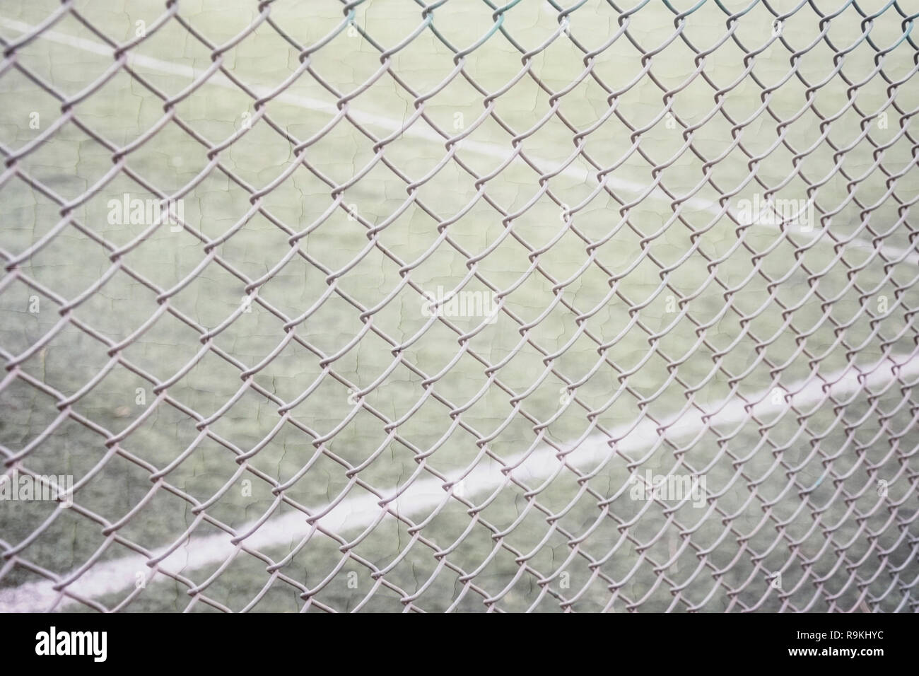 Tennis court fencing with netting netting against the background of the court and marking with white paint sports texture overlay texture - Stock Image