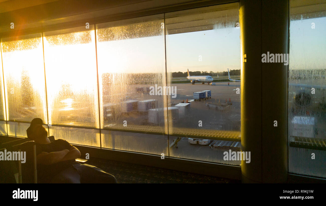 Sleeping  traveler with rising sun in sparsly crowded terminal, Orlando International Airport, FL - Stock Image