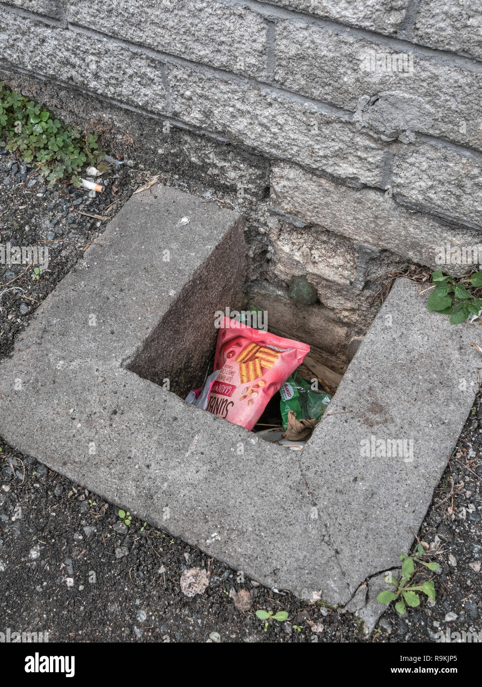 Plastic food wrapper discarded in urban drain. Metaphor plastic pollution, environmental pollution, war on plastic waste, plastic rubbish. Stock Photo