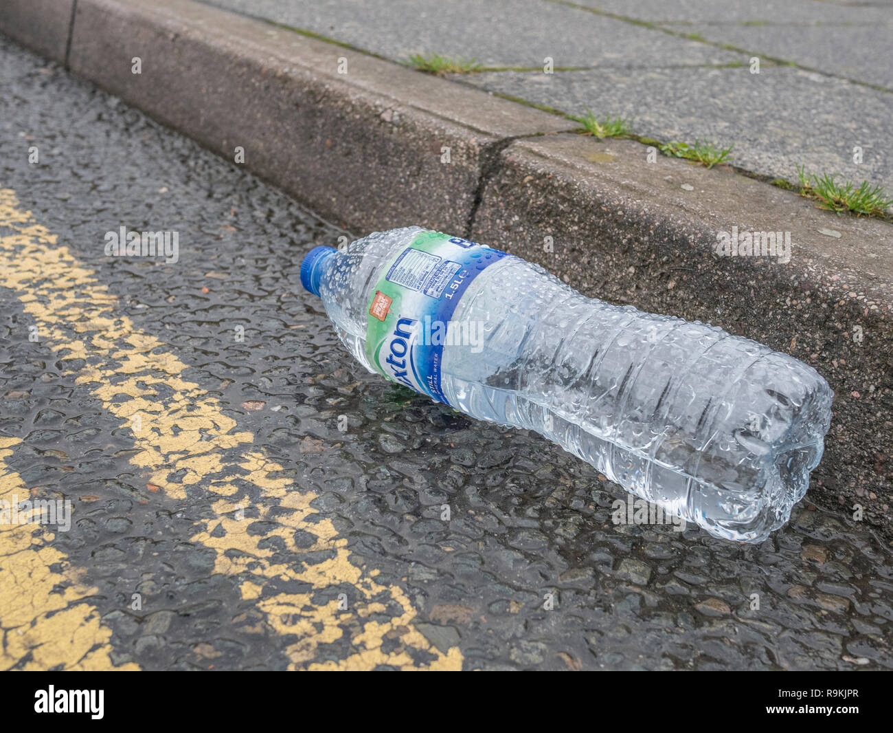 Empty PTFE plastic mineral water bottle discarded in urban road gutter. Metaphor plastic pollution, environmental pollution, war on plastic waste. - Stock Image