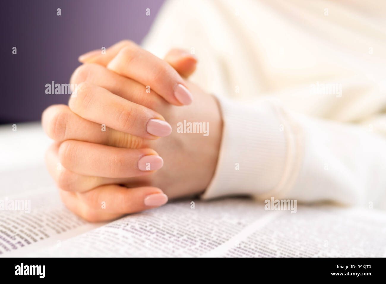 Unrecognizable woman reading big book - Holy Bible and praying. Christian studying scripture. Student in the college library preparing for exams. Lear - Stock Image