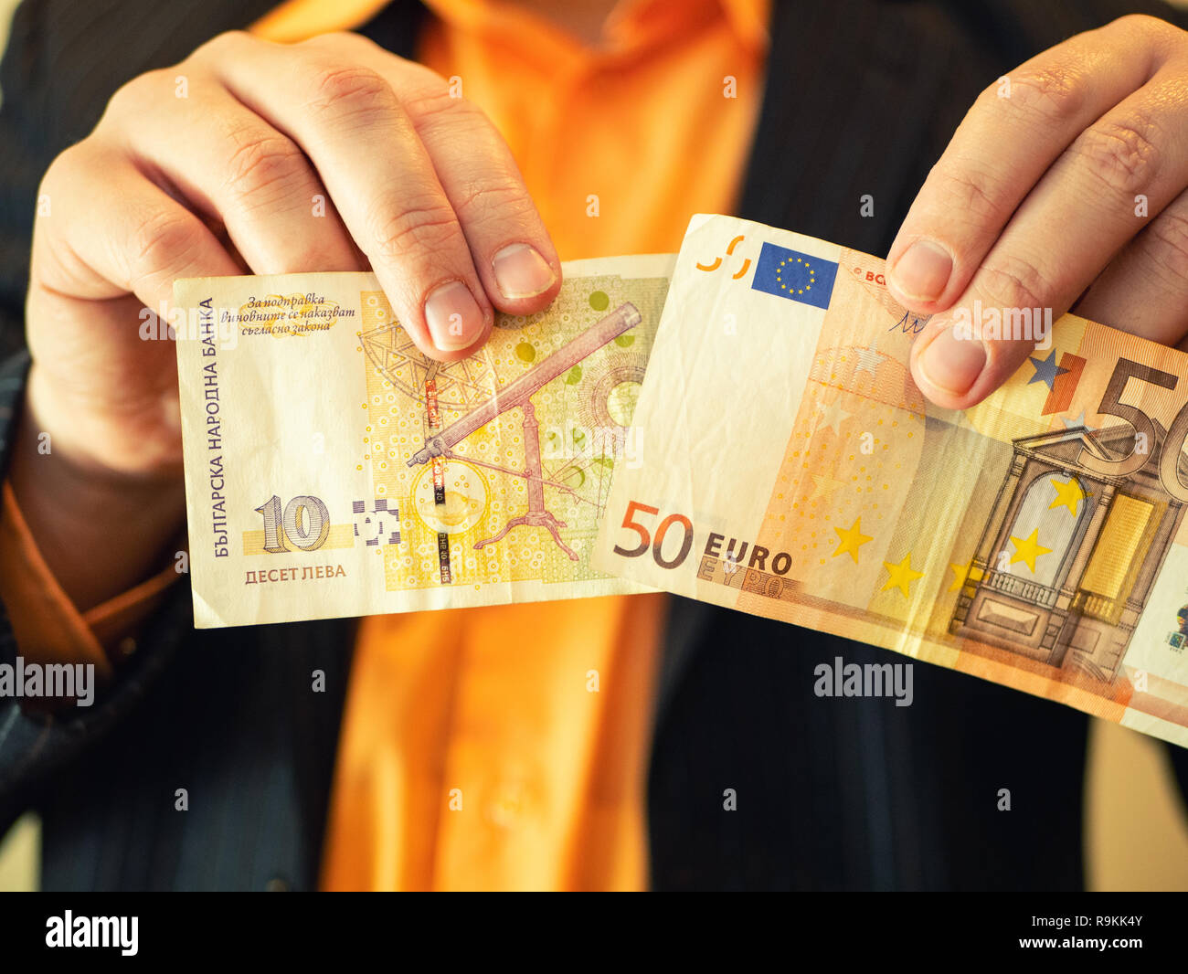 closeup of man hands show Bulgarian lev money in one and fifty Euros in other hand. concept of Bulgaria integration to European Union EU - Stock Image