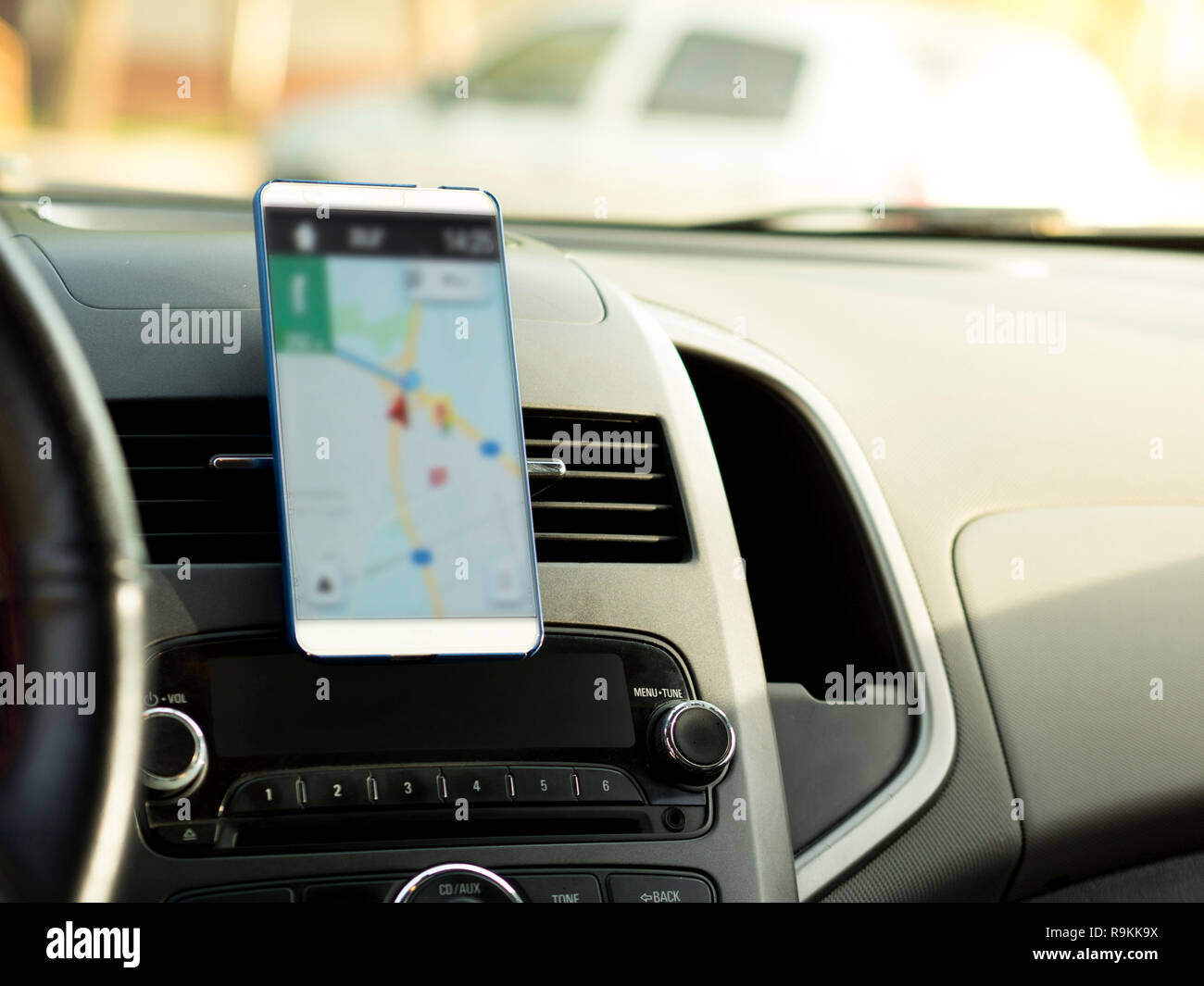 mobile phone located in the center of the vehicle console. Blank screen phone in the car - Stock Image