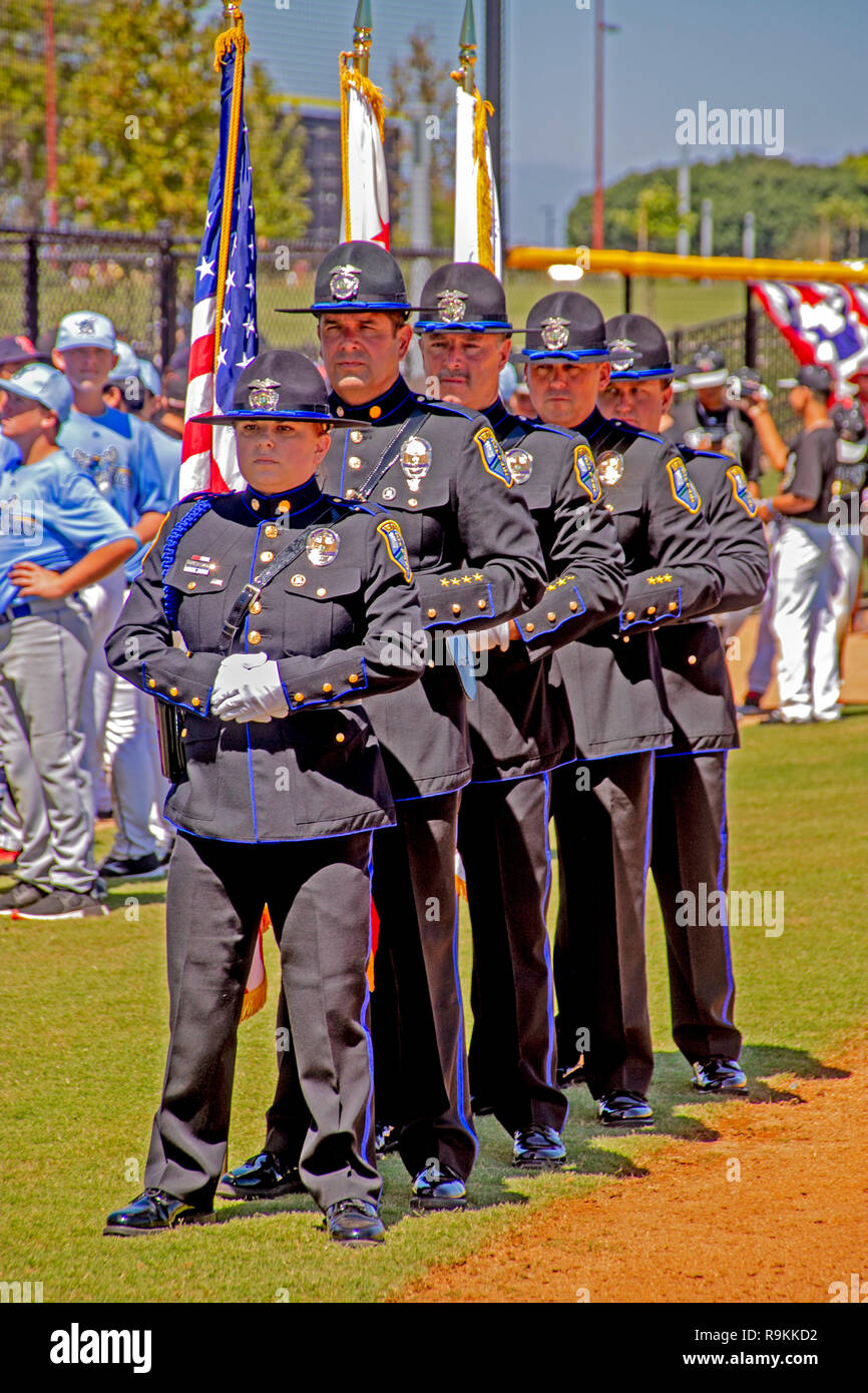 A stoical policewoman joins her male colleagues in dress uniform as they participate in the dedication of a softball stadium in Irvine, CA. - Stock Image