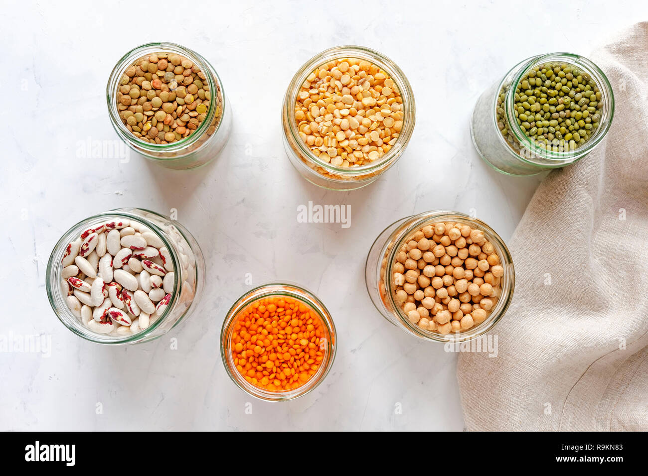 Open glass jars full of assorted dried legumes with mung beans, beans, lentils and peas over a white background Stock Photo