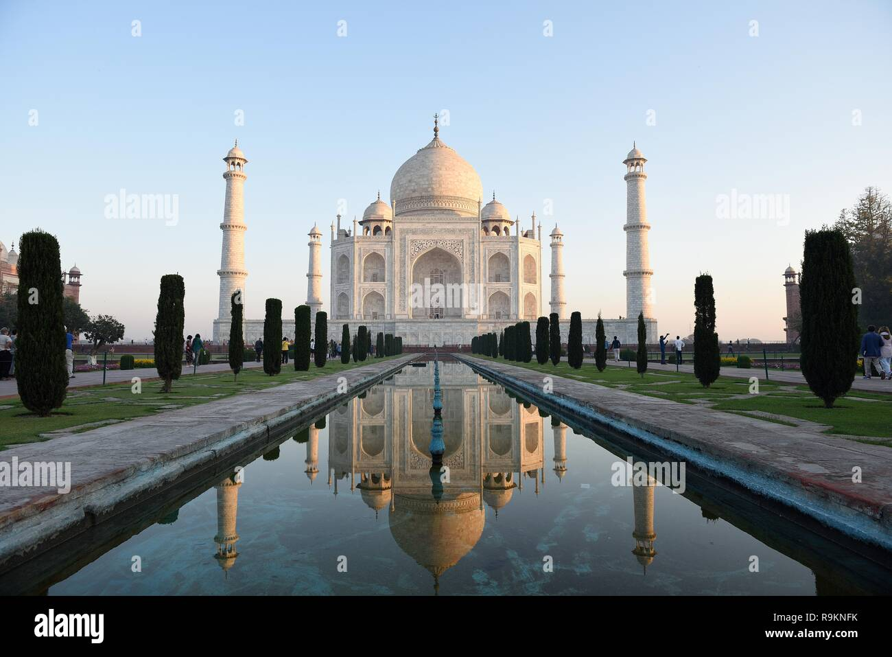 Famous white marble Taj Mahal with water reflections at sunrise in Agra, India. - Stock Image