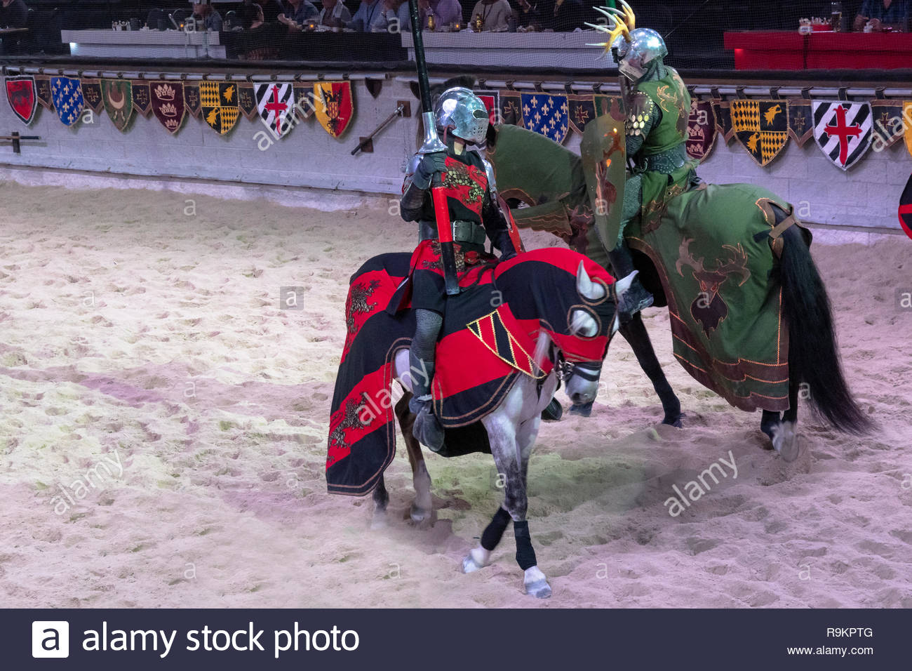 Medieval Times restaurant and jousting. Two adversaries take their places as they cross each other in the arena. The famous place is a tourist attract - Stock Image