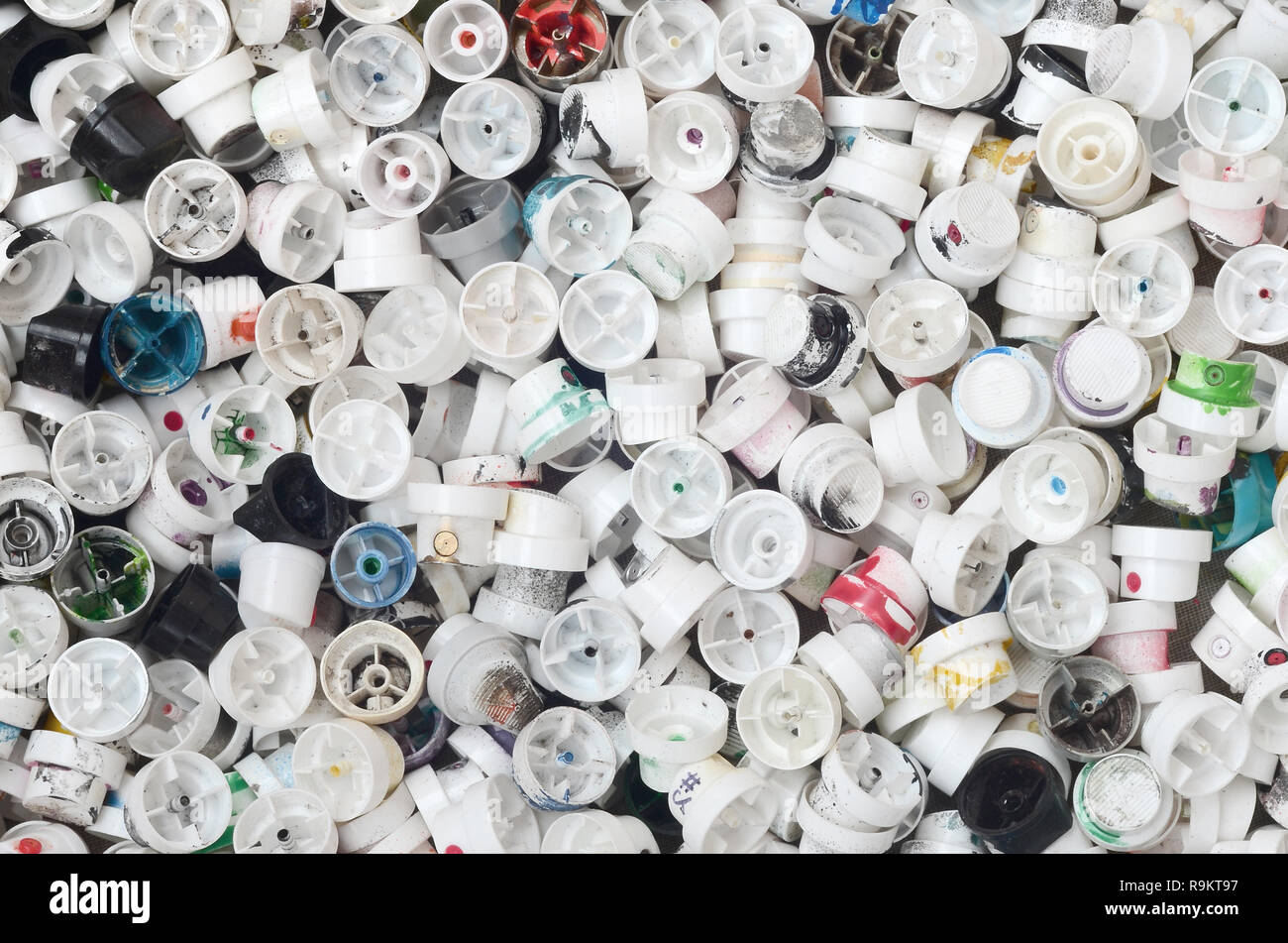 A pattern of many used and soiled nozzles from spray cans with aerosol paint. Background texture of the street art of drawing graffiti on the walls Stock Photo