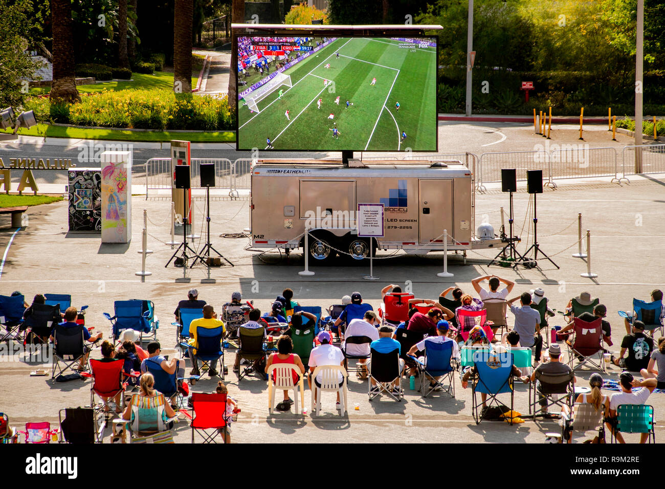 A daytime audience watches a World Cup soccer game on a giant outdoor television screen in Costa Mesa, CA. Stock Photo