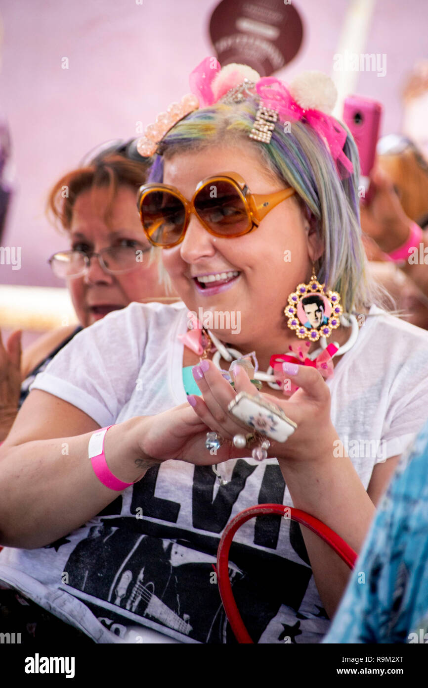 An enthusiastic woman in the audience of an Elvis Presley impersonation rock and roll music festival in Fullerton, CA, wears photos of Elvis in her earrings and an Elvis T shirt as she applauds the performers. Stock Photo