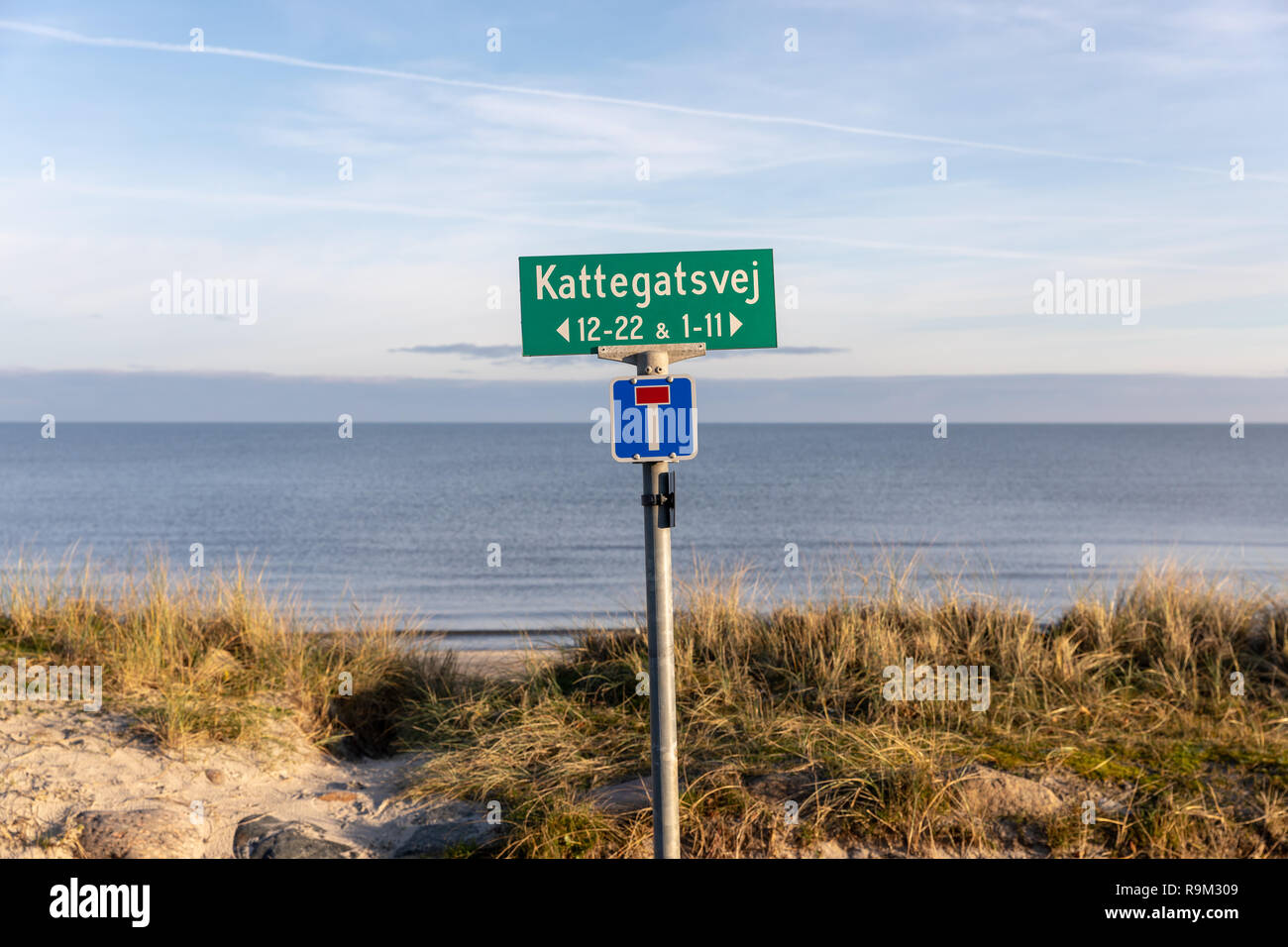 Kattegatsvej, street name sign by the beach, with the sea (Kattegat) in the background; Saeby, Denmark - Stock Image