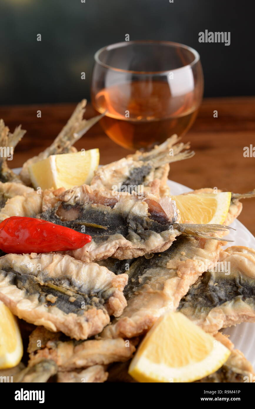 Sardines breaded and fried on plate with lemon wedges and a chili - Stock Image
