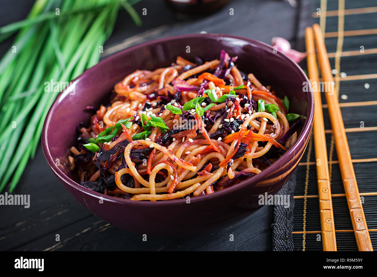 Chinese food. Vegan stir fry noodles with red cabbage and carrot in a bowl on a black wooden background. Asian cuisine meal. Stock Photo