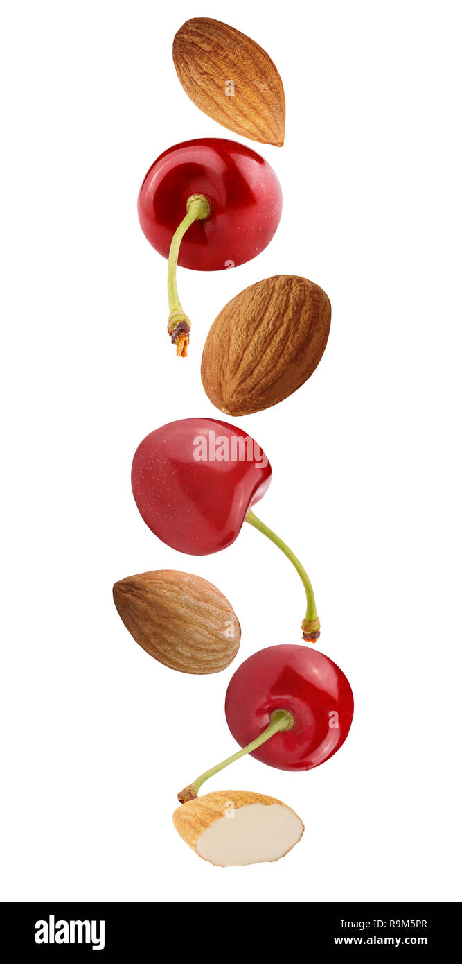Isolated falling fruits. Flying cherry and almonds isolated on white background with clipping path as package design element and advertising. Full dep - Stock Image