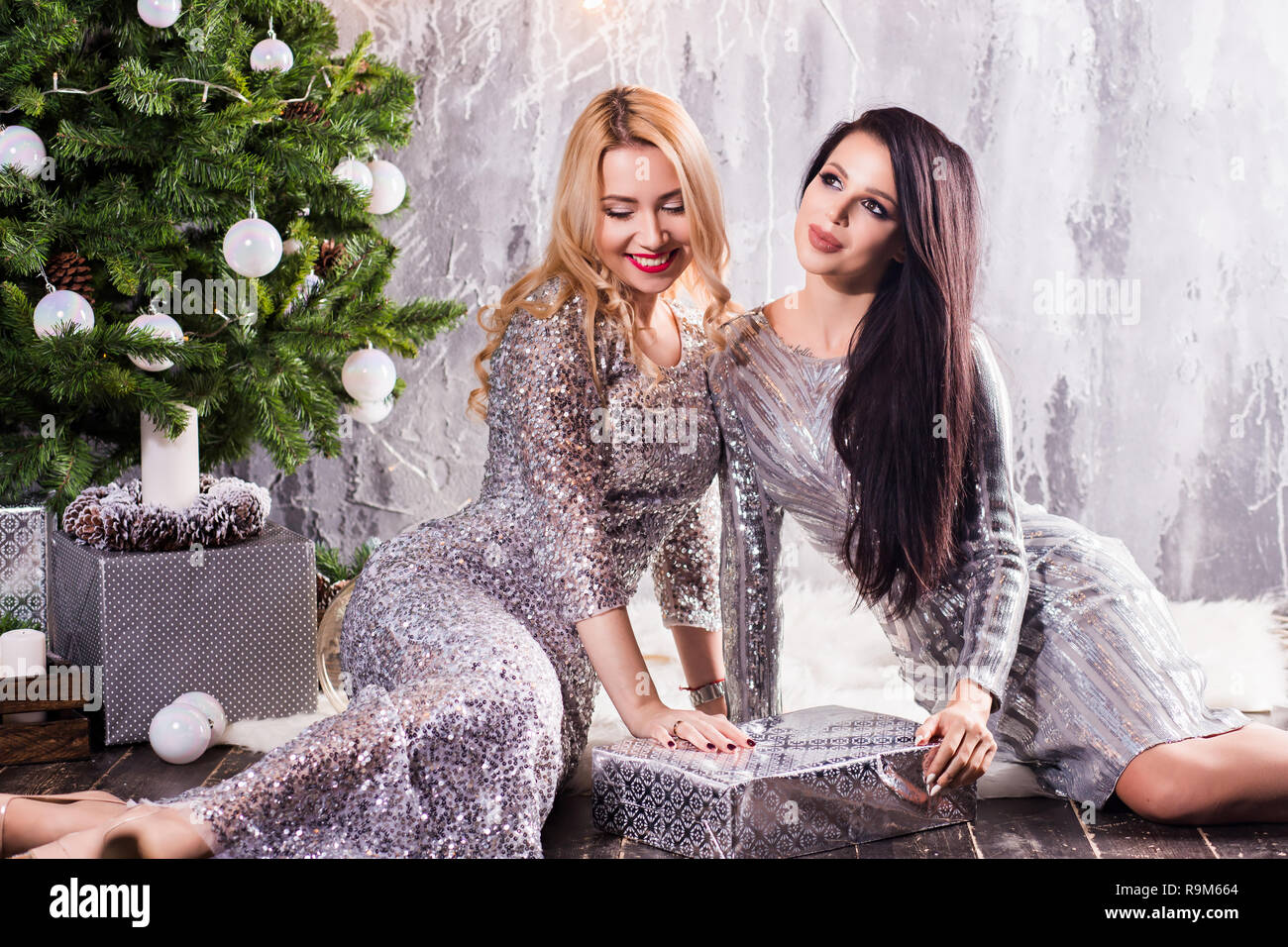 Christmas Evening Dresses.Two Girls In Evening Dresses Near The Christmas Tree The