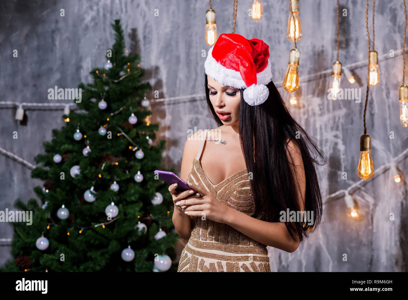 stylish woman holding phone looking at screen at christmas tree lights. wearing santa hat smiling. seasonal greetings concept. space for text. Holiday - Stock Image