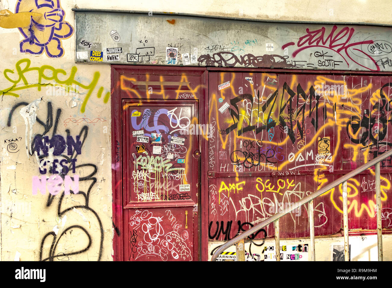 Boarded up red door and window covered in graffiti and spray paint , Montmartre Paris - Stock Image