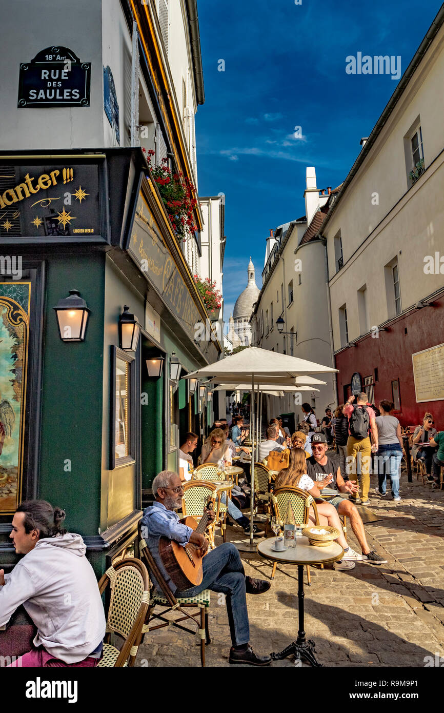 A man sitting playing a guitar outside de La Bonne Franquette, a cafe,  restaurant  ,whilst  people enjoy lunch in the sunshine ,Montmartre, Paris - Stock Image