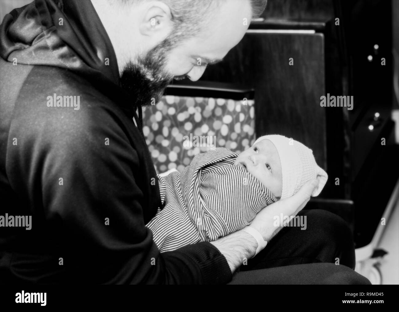 Father Holds Newborn Baby Boy Wrapped in a Blanket As He Looks up at His Dad. Black & White Photo. - Stock Image