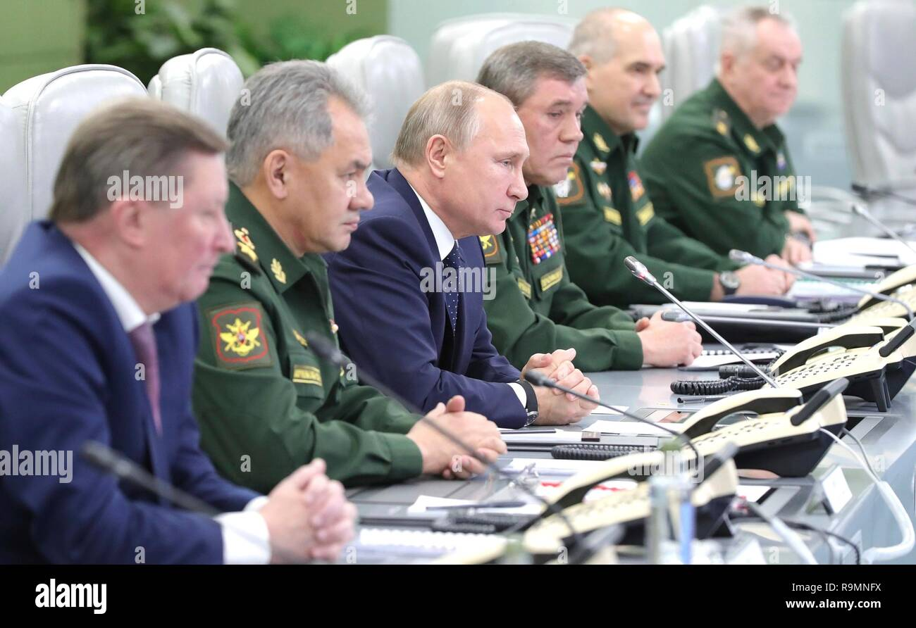 Moscow, Russia. 26th December, 2018. Russian President Vladimir Putin, center, alongside Defense Minister Sergei Shoigu, left, and Army Chief Gen. Valery Gerasimov, right, during a test firing of the Avangard hypersonic glide vehicle from the National Centre for State Defence Control room December 26, 2018 in Moscow, Russia. The Avangard was launched from the Dombarovskiy missile base in the southern Ural Mountains. Credit: Planetpix/Alamy Live News - Stock Image
