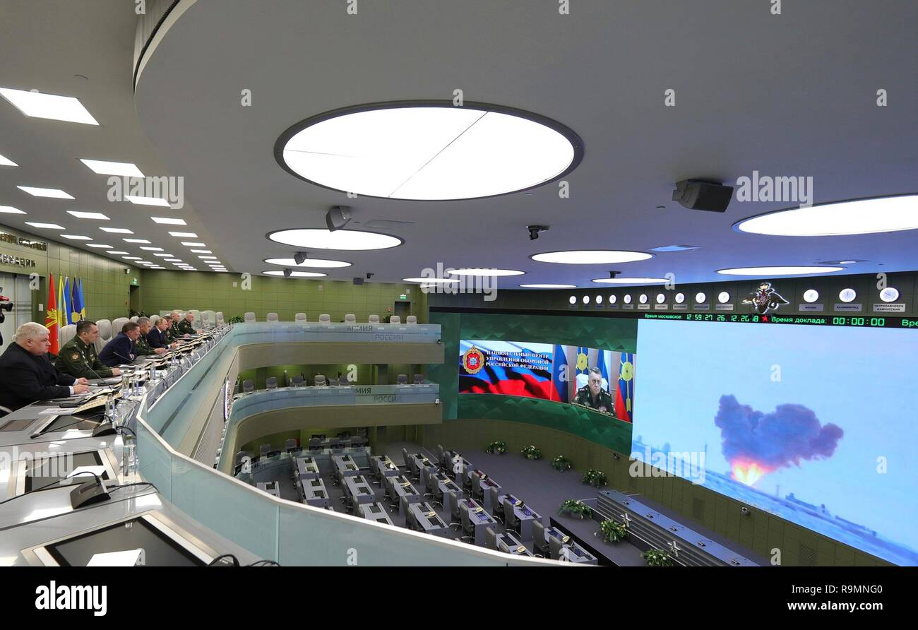 Moscow, Russia. 26th December, 2018. Russian President Vladimir Putin, left, alongside Defense Minister Sergei Shoigu, and Army Chief Gen. Valery Gerasimov, watch a video feed of a test firing of the Avangard hypersonic glide vehicle from the National Centre for State Defence Control room December 26, 2018 in Moscow, Russia. The Avangard was launched from the Dombarovskiy missile base in the southern Ural Mountains. Credit: Planetpix/Alamy Live News - Stock Image