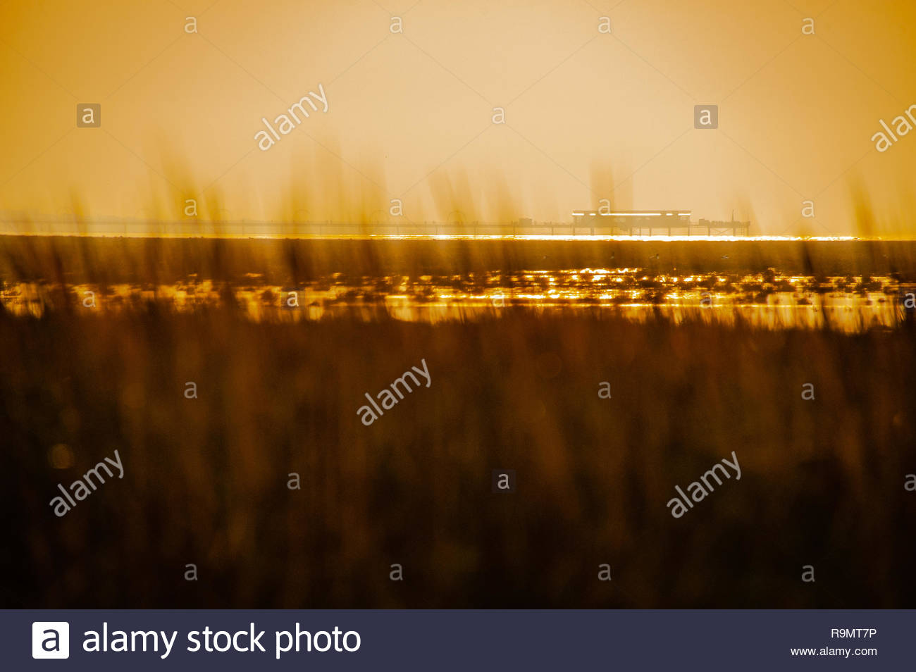 UK Weather, Southport, Merseyside, England, UK. 26th Dec, 2018. A largely grey murky Boxing day afternoon at RSPB Marshside Nature Reserve, with occasional flashes of sunlight, as the afternoon light starts to fade over Southport Pier, view from across the Marshes, Southport, Merseyside, Lancashire, England UK Credit: Christopher Canty Photography/Alamy Live News Stock Photo
