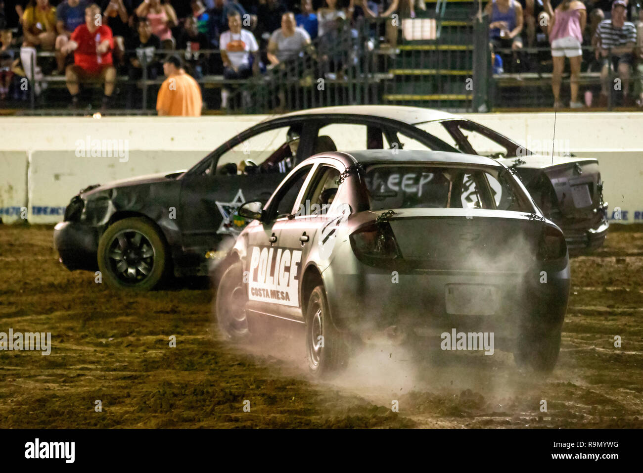 Cars head for a crash in a night time demo derby for police officer drivers at a Costa Mesa, CA, stadium. - Stock Image
