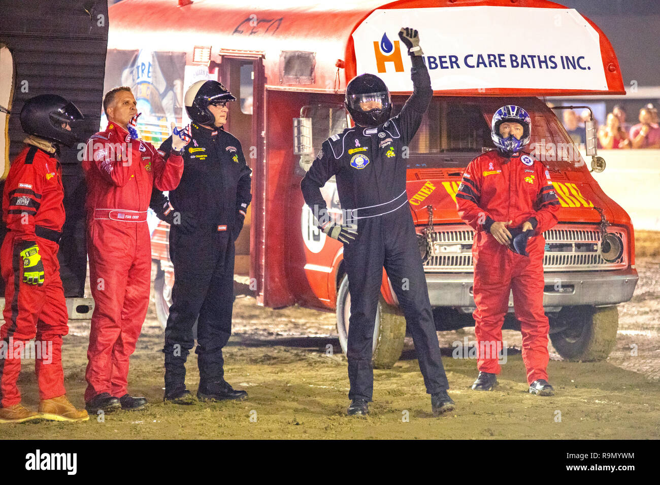 A uniformed police officer waves to the audience as he joins colleagues in safety coveralls in a police-only motor home demo derby in a Costa Mesa, CA, stadium. - Stock Image