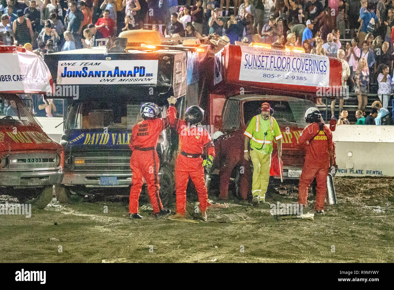Drivers in safety clothes and crash helmets congratulate each other with high fives at the finish of a motor home demo derby in a Costa Mesa, CA, stadium. - Stock Image