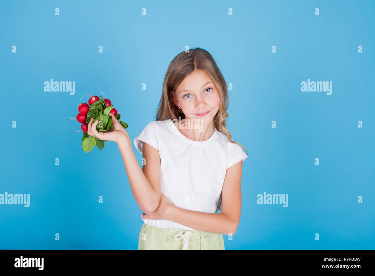 little girl with fresh vegetables red radishes - Stock Image