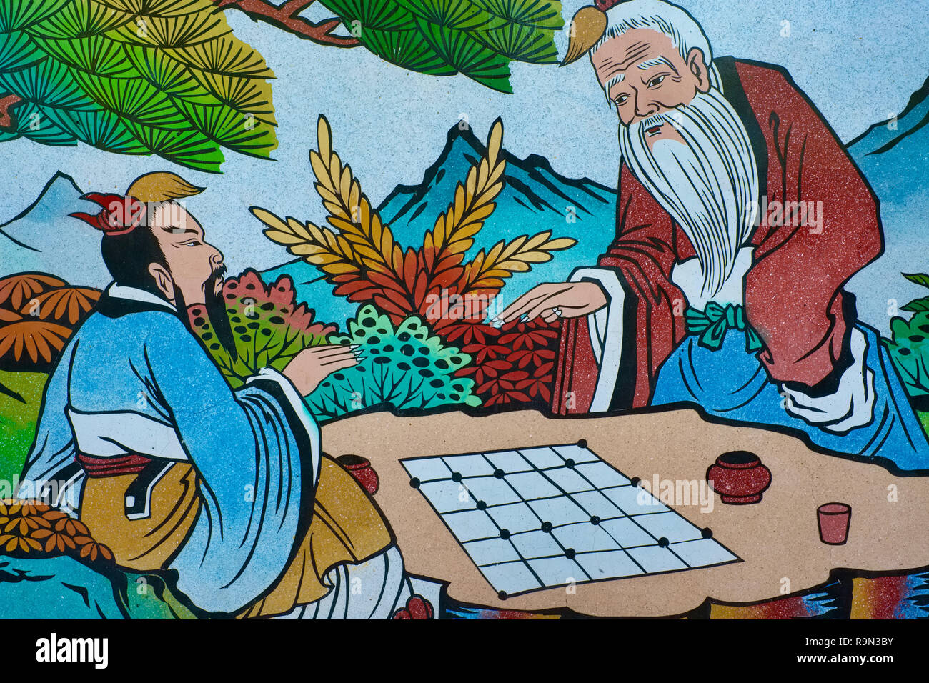 A painting on the outer wall of Sanjao Tha Ruea, a Taoist temple in Tha Ruea, Phuket, Thailand, showing a historical scene of a game of Chinese chess - Stock Image