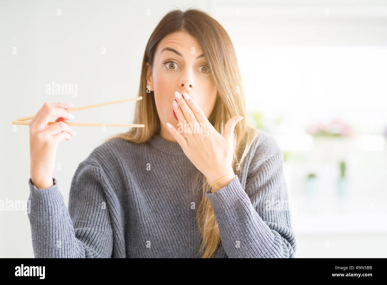 Young beautiful woman holding asian chopsticks at home cover mouth