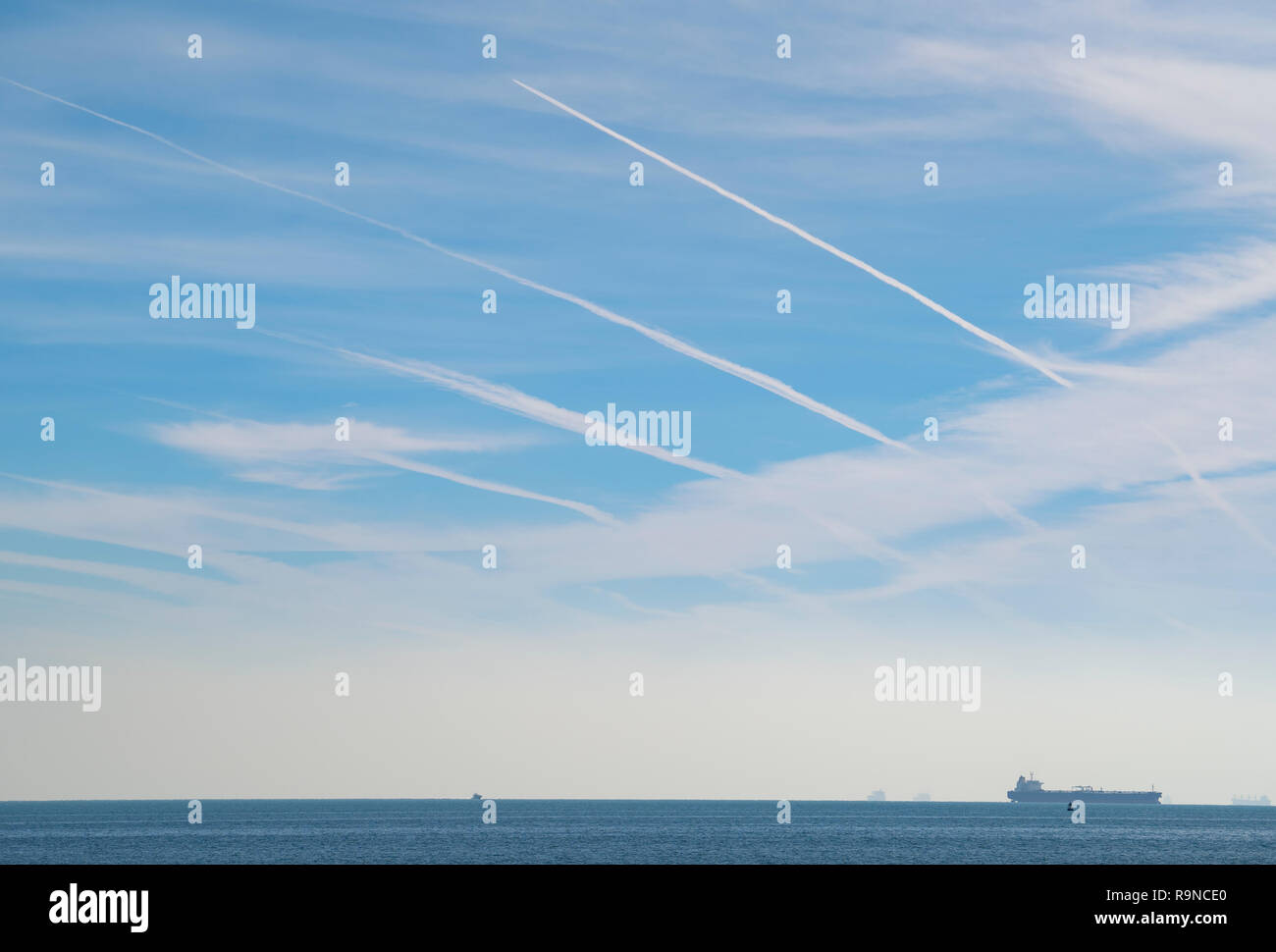 Many contrails from passenger aircraft from emirates airline A380s flying north past Kuwait from Dubai en route to Europe. - Stock Image