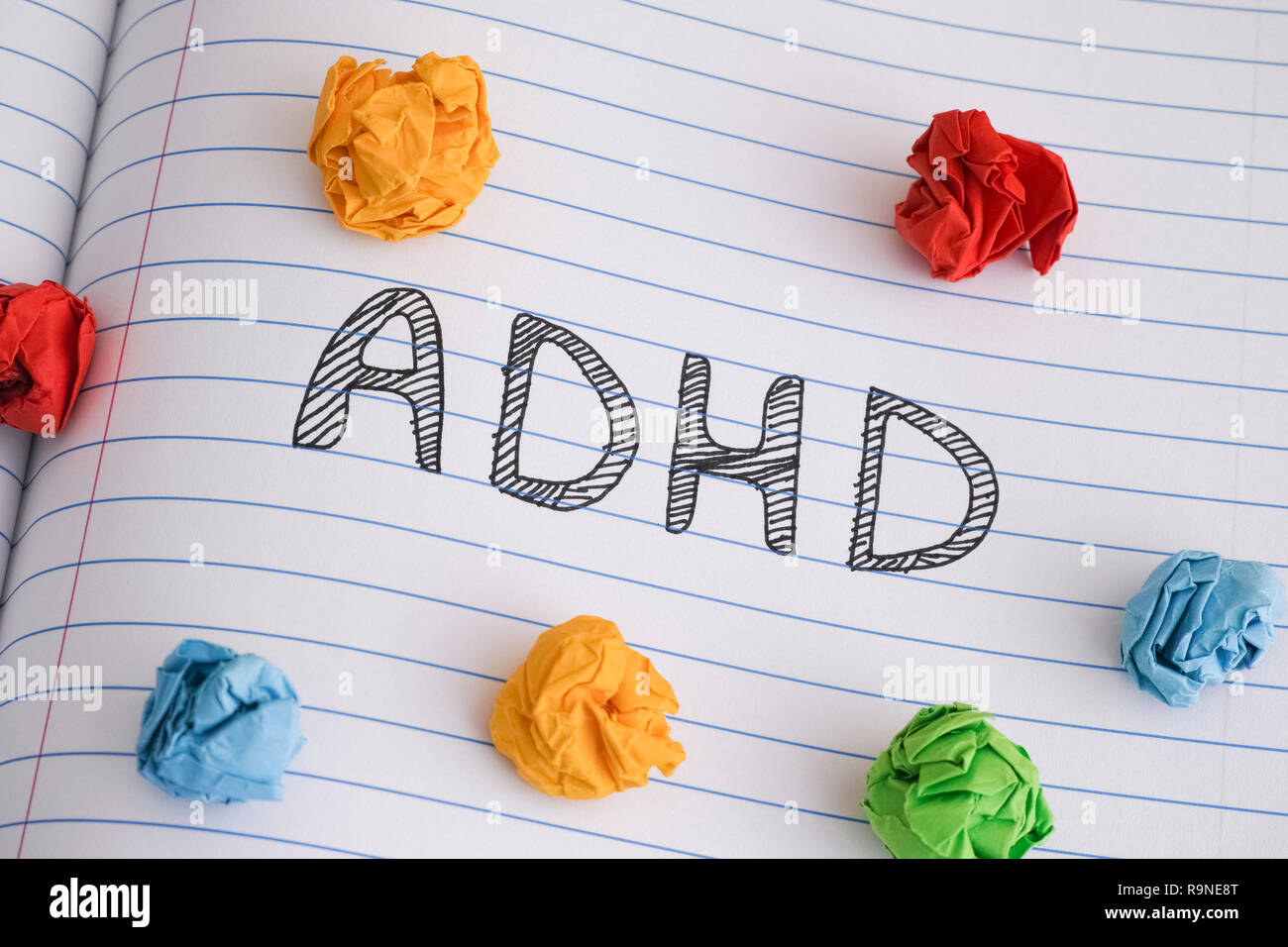 ADHD. Abbreviation ADHD on notebook sheet with some colorful crumpled paper balls on it. Close up. ADHD is Attention deficit hyperactivity disorder. - Stock Image