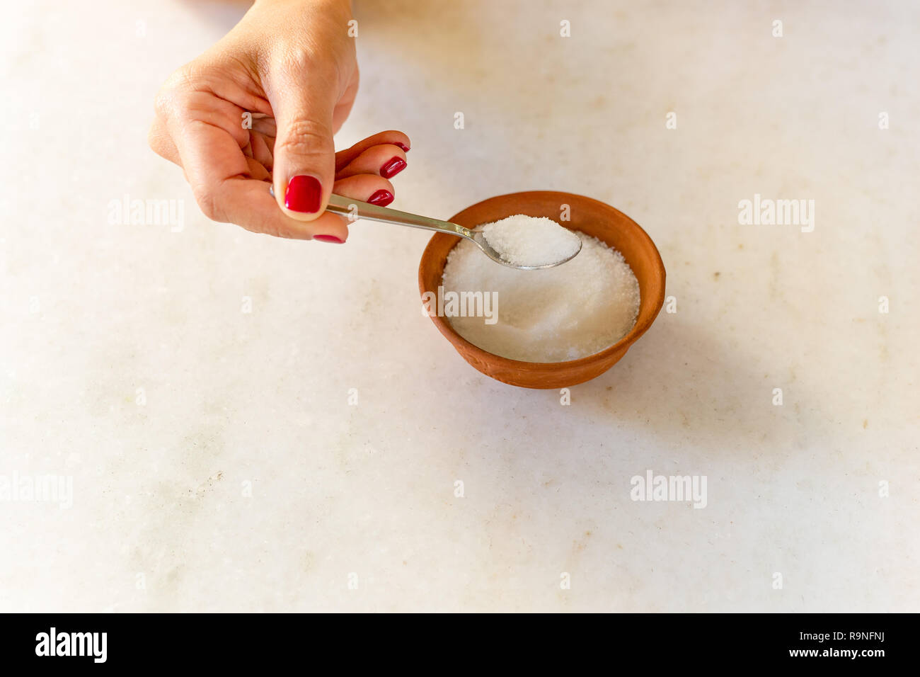 Woman hand holding spoon full of sugar health care concept. - Stock Image