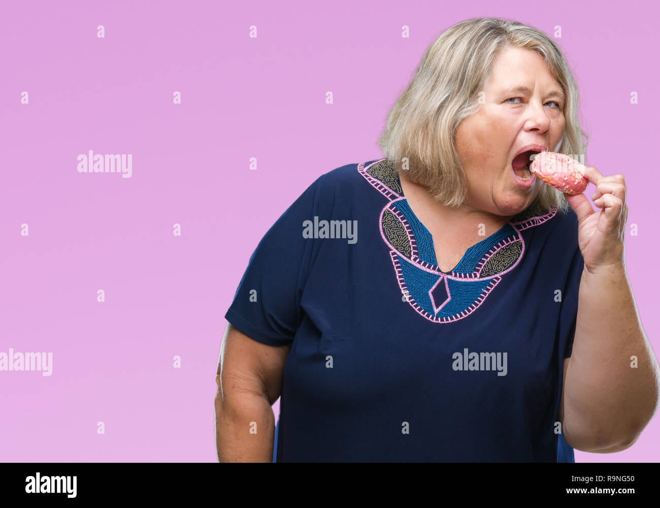 fbc74436b33 Senior plus size caucasian woman eating sugar donut over isolated background  with a confident expression on smart face thinking serious