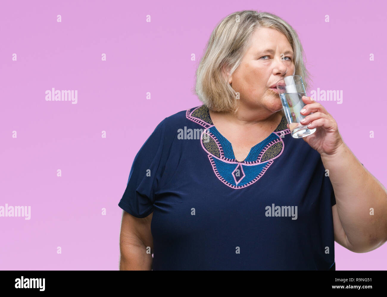 c347f19b283 Senior plus size caucasian woman drinking glass of water over isolated  background with a confident expression
