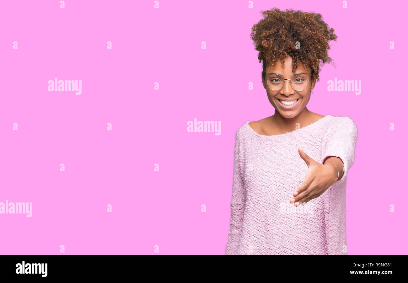 Beautiful young african american woman wearing glasses over isolated background smiling friendly offering handshake as greeting and welcoming. Success Stock Photo
