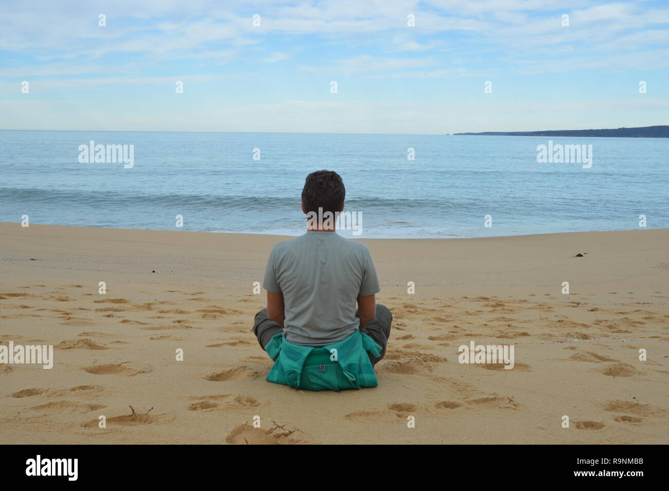 Man sitting cross legged, gazing out to sea, relaxing and thinking about the world. - Stock Image
