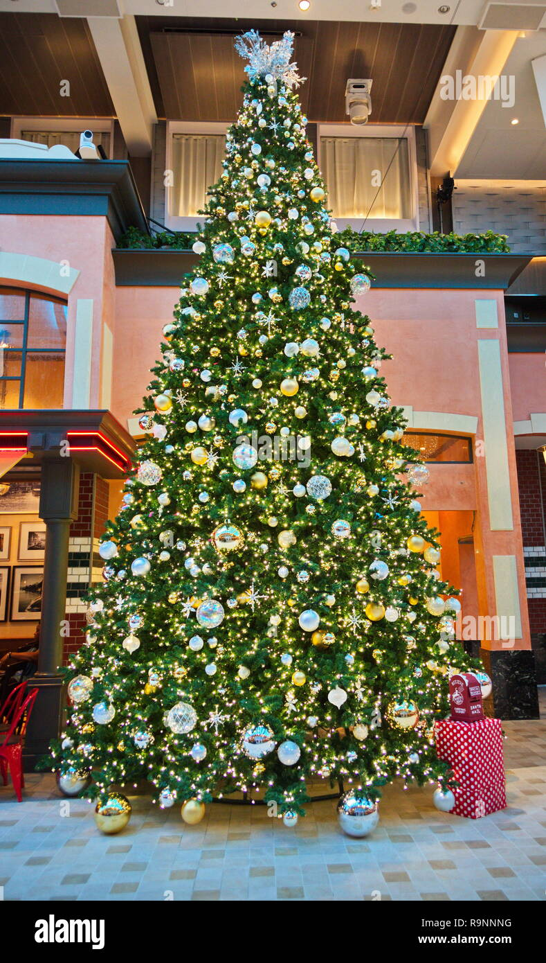 Many Gold And Silver Ornaments With Lights On A Green Christmas Tree In The Lobby Of A Cruise Ship Stock Photo Alamy