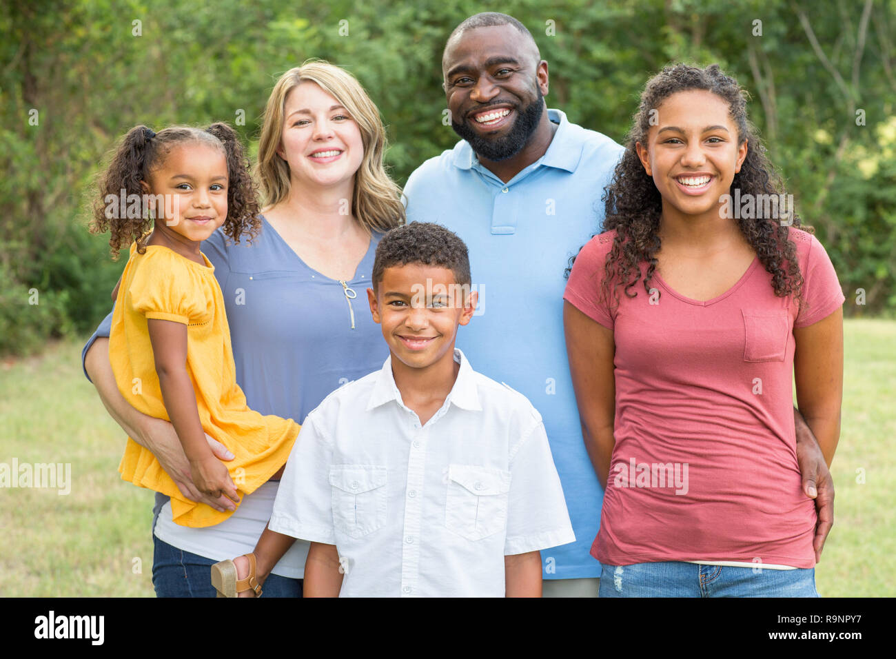 Portarit of a happy mixed race family smiling - Stock Image