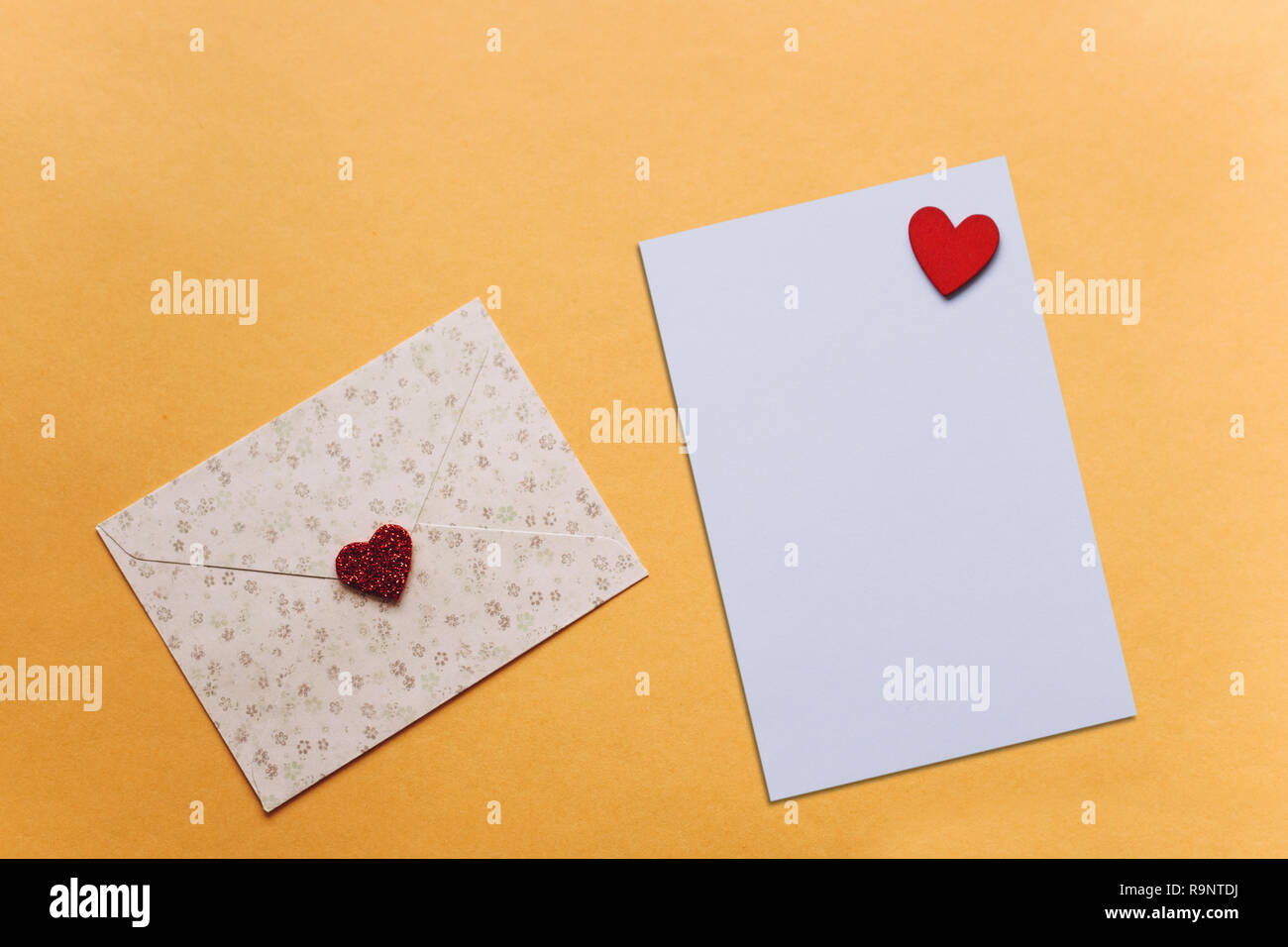 Blank sheet with red heart for text or write. Near an envelope with a heart to send. Concept for Valentine's Day or Women's Day or Mother's Day. - Stock Image